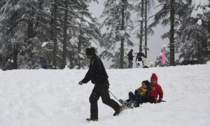 An Indian man pulls a tourist on a sledge through snow at Patnitop in Udhampur district of Jammu and Kashmir state, India, Sunday, Jan.8, 2017. The Kashmir region remained cut off from the rest of the country for the third consecutive day Sunday. (AP Photo/Channi Anand)